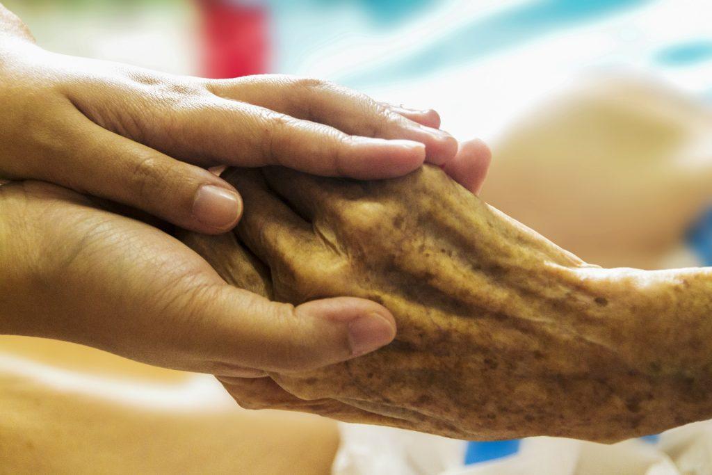 Nurse holding an elderly hand